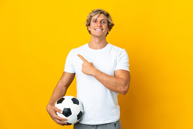 Английский футболист на изолированном желтом фоне, указывая в сторону, чтобы представить продукт