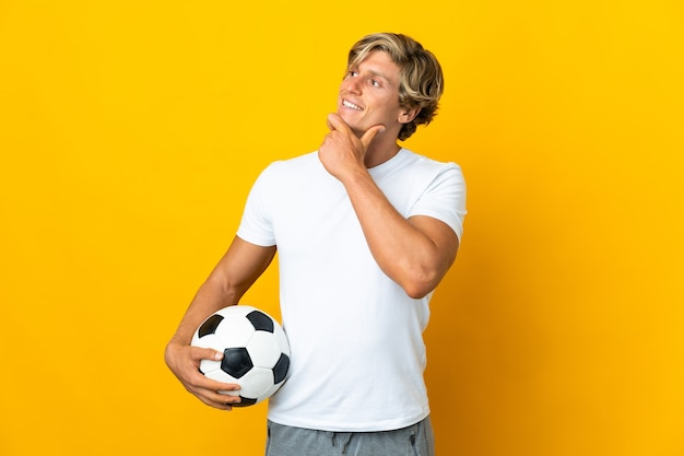 横を見て笑っている孤立した黄色の壁の上の英国のサッカー選手