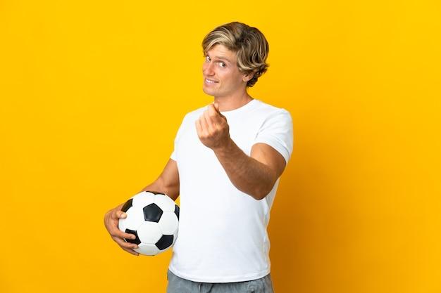 Английский футболист над изолированной желтой стеной делает денежный жест