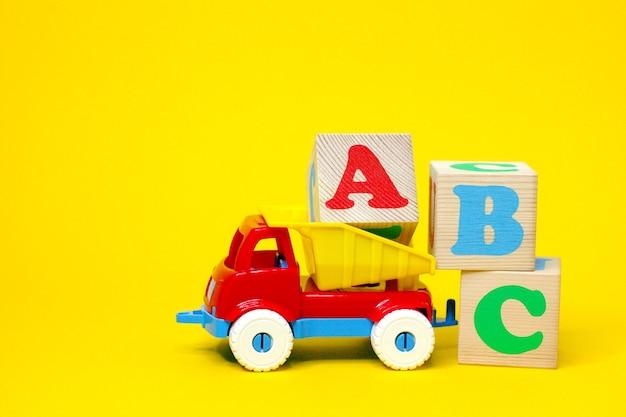 黄色の背景のおもちゃのプラスチックトラックの木製ブロックに英字abc。外国語を学ぶ。初心者のための英語。