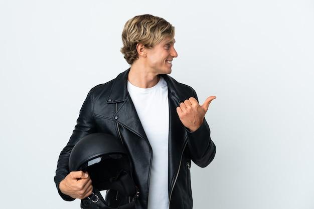 製品を提示するために側面を指しているオートバイのヘルメットを保持しているイギリス人男性