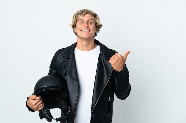 Англичанин держит мотоциклетный шлем, указывая в сторону, чтобы представить продукт