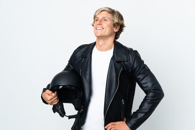 엉덩이에 팔을 포즈와 미소 오토바이 헬멧을 들고 영어 남자
