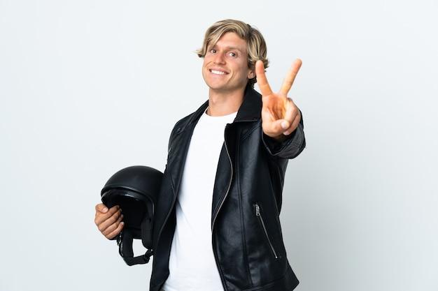 Английский мужчина держит мотоциклетный шлем улыбается и показывает знак победы
