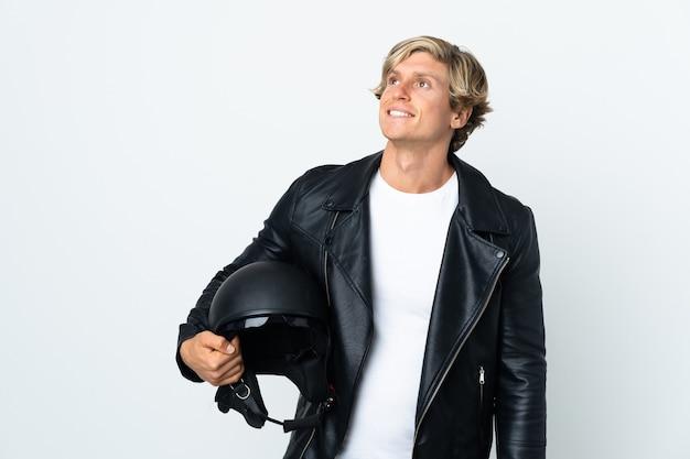 Англичанин, держащий мотоциклетный шлем, думает об идее, глядя вверх