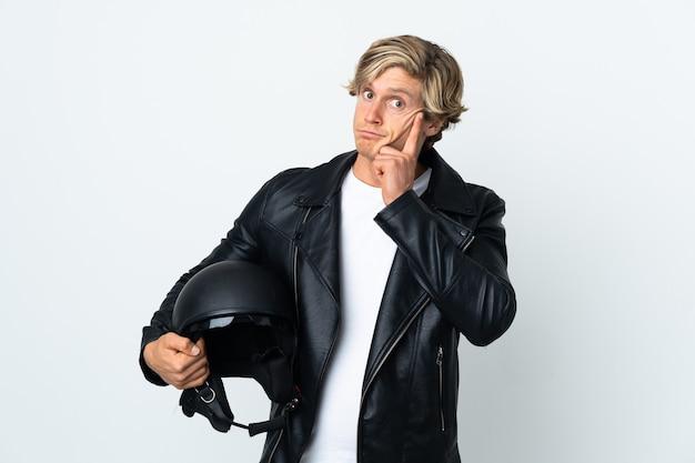 Англичанин, держащий мотоциклетный шлем, думает об идее