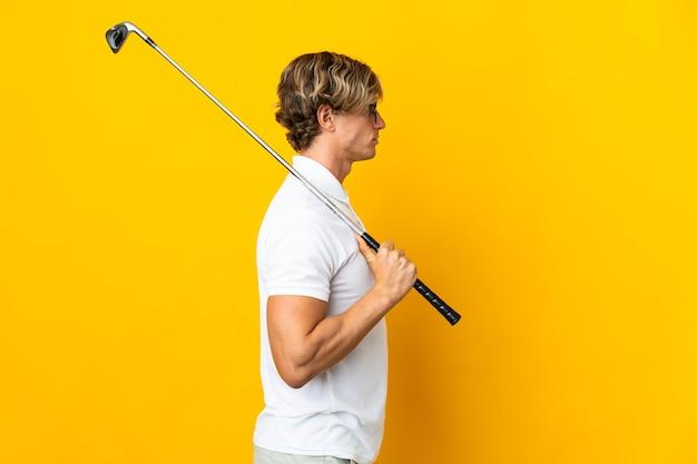 Английский мужчина изолирован, играя в гольф в боковом положении