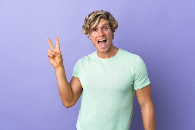 English man over isolated purple background smiling and showing victory sign
