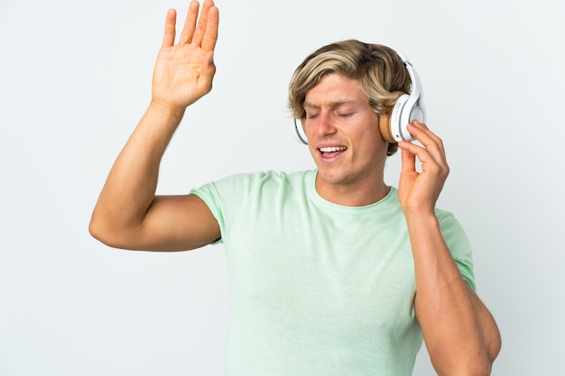 English man over isolated white wall listening music and dancing