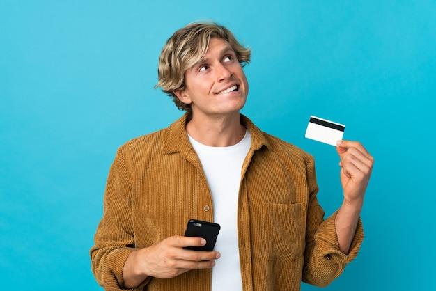 Англичанин на изолированном синем фоне покупает с мобильного с помощью кредитной карты, думая
