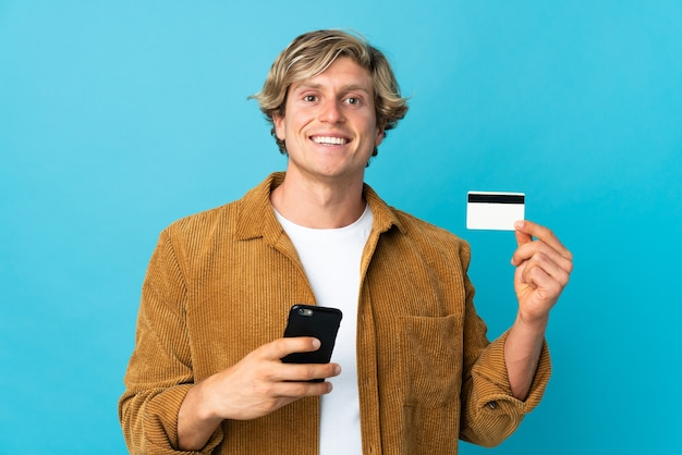 Англичанин над изолированной синей стеной покупает мобильный телефон с помощью кредитной карты
