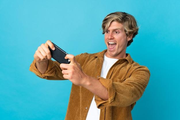 Англичанин над изолированной синей стеной играет с мобильным телефоном