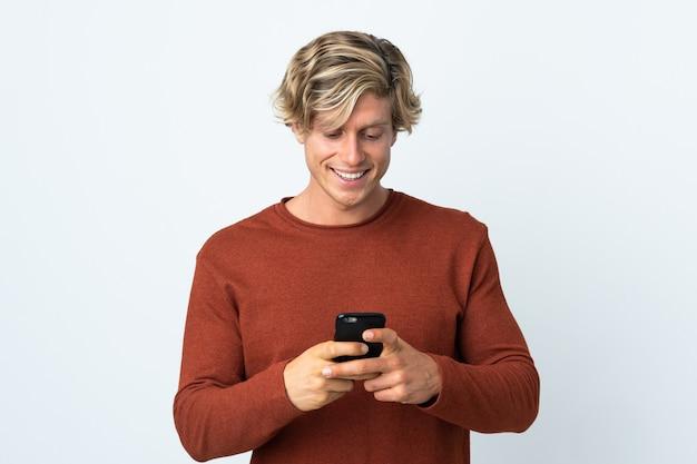 携帯電話でメッセージを送信する孤立した白い背景の上のイギリス人