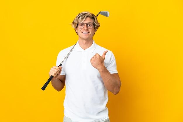 Англичанин над изолированным белым играет в гольф и с большими пальцами руки вверх, потому что произошло что-то хорошее