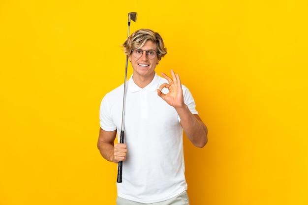Английский человек над изолированным белым играет в гольф, делая знак ок