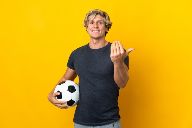サッカーボールと来たるジェスチャーをしている孤立した黄色の壁の上のイギリス人