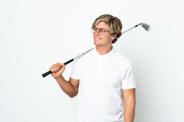 Английский мужчина играет в гольф, глядя в сторону и улыбается