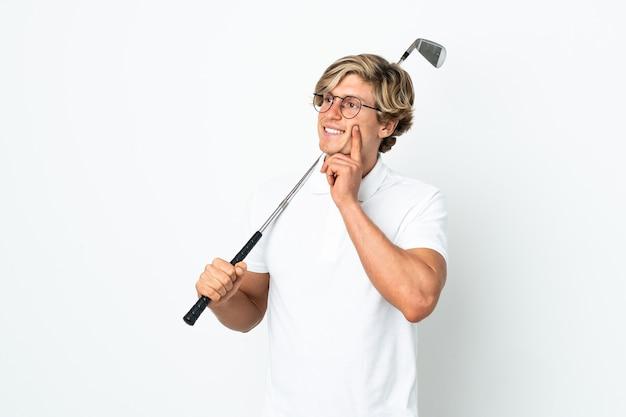 Английский мужчина играет в гольф, думая об идее, глядя вверх