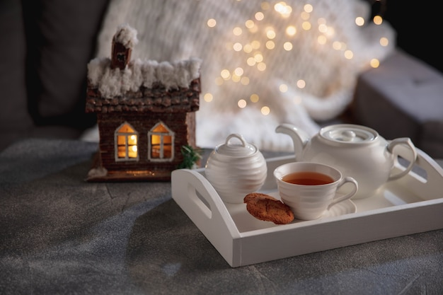 英語のお茶と木製の灰色のテーブル、クローズアップのケーキ。ティーセット付きの白い木製トレイ。家の雰囲気と快適さ、ロマンチックなデート、冬、家の快適さ、屋内、クリスマスまたは新年の概念。