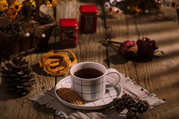 Время английского чая. чашка чая с печеньем на деревянном столе, домашний интерьер в деревенском стиле.
