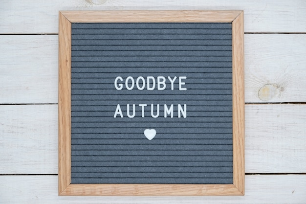 English text goodbye autumn on a letter board in white letters on a gray background and a symbol of heart.
