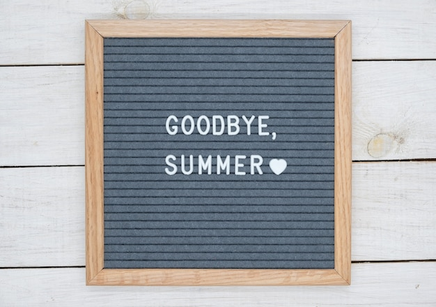 English text goodbye summer on a letter board in white letters on a gray background and a symbol of heart.