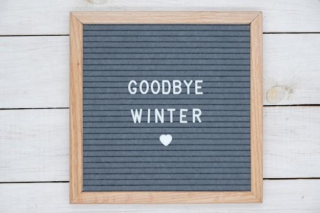 Английский текст до свидания зимой на доске для писем белыми буквами на сером столе
