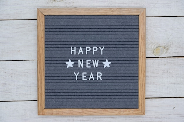 English text happy new year and two stars on a felt board in a wooden frame. white letters on a gray background.