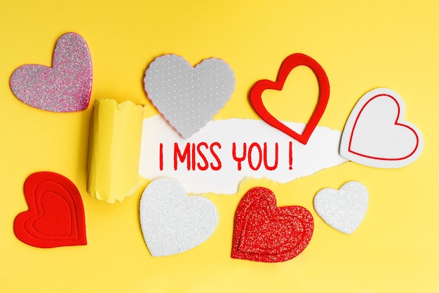 English text i miss you written in red letters on a yellow card with love hearts.