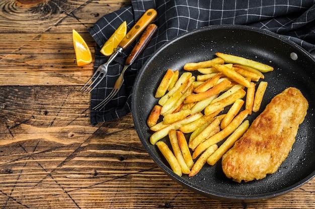 Английское традиционное блюдо из рыбы с жареным картофелем на сковороде. деревянный фон. вид сверху. скопируйте пространство.