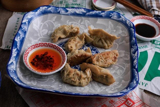 英語訳:gyoza、キャベツを詰めた蒸し餃子、唐辛子油を添えた中国の青いプレートで提供