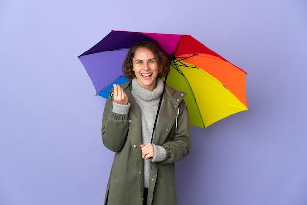 Англичанка, держащая зонтик на фиолетовой стене делает денежный жест
