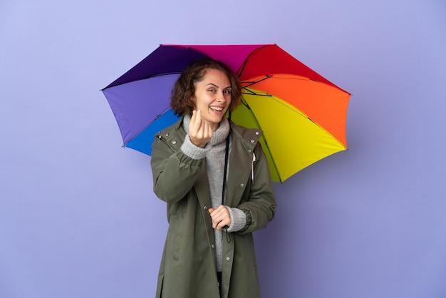 Англичанка держит зонтик на фиолетовом фоне, делая денежный жест