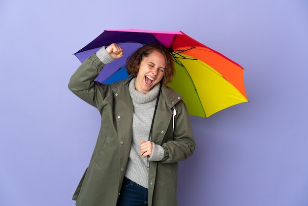 English woman holding an umbrella isolated on purple background celebrating a victory