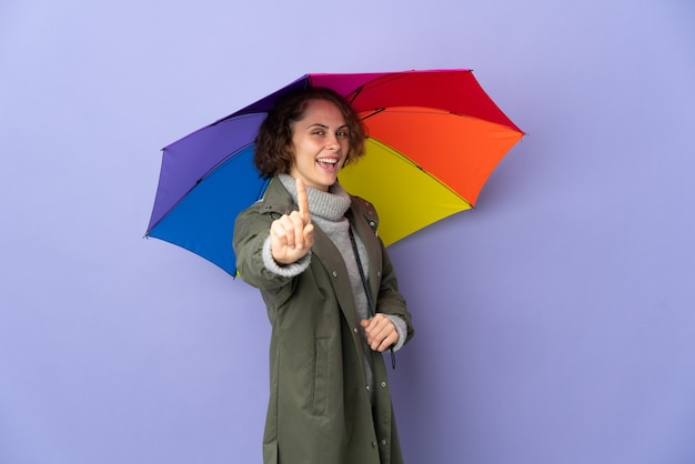 English woman holding an umbrella on purple background showing and lifting a finger