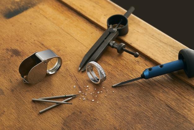 조각사 주 얼러 작업 도구 및 다이아몬드가 세팅 된 약혼 금반지