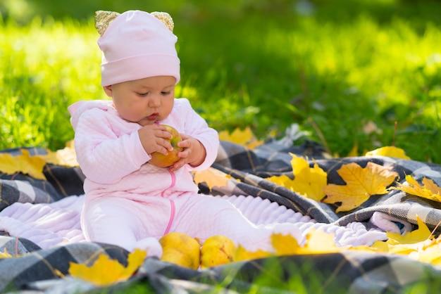 色とりどりの葉に囲まれた秋の公園の毛布の上に座って、新鮮なリンゴを調べている夢中の小さな女の赤ちゃん