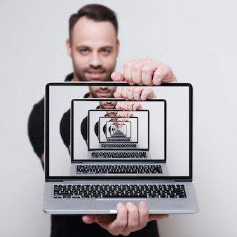Enigmatic surrealistic optical illusion. close-up of laptop in hands of smiling man on grey studio background.