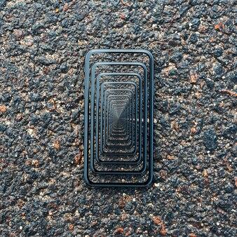 Enigmatic surrealistic optical illusion. close-up of smartphone on wet asphalt.