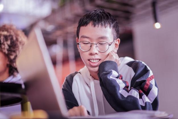 Загадочная улыбка. счастливый азиатский подросток трогает его щеку, глядя на тетрадь