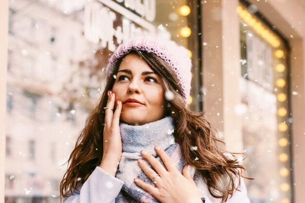コートと帽子の若い美しい女性の肖像画をenjoingのfi