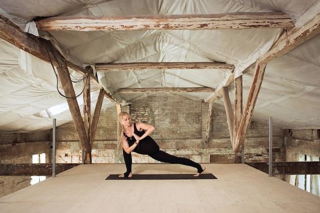 즐겨. 젊은 체육 여자 버려진 된 건설 건물에 요가 연습. 정신적 및 신체적 건강 균형. 건강한 라이프 스타일, 스포츠, 활동, 체중 감소, 집중력의 개념.