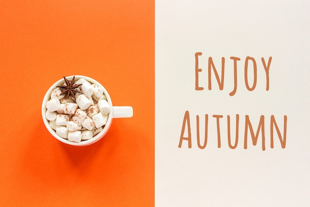 Enjoy autumn text and cup of cocoa with marshmallows on orange beige background. concept fall mood.