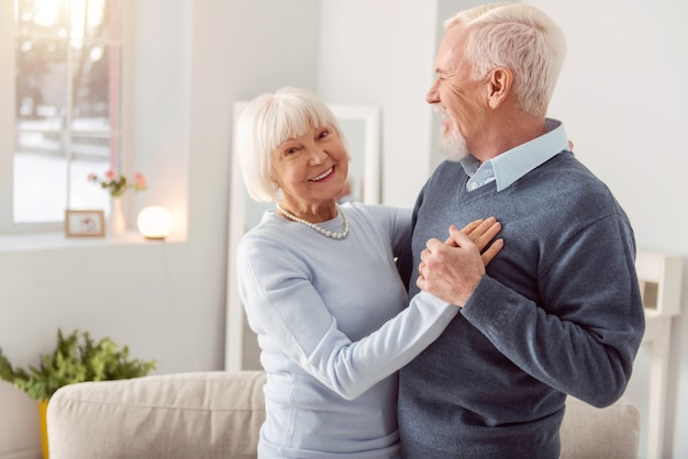Enjoy dancing. happy charming elderly woman smiling while dancing waltz with her husband in the living room