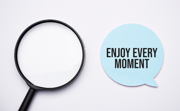 Enjoy every moment speech bubble and black magnifier isolated on the yellow background.