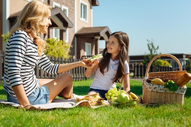 그것을 즐기십시오. 양탄자에 앉아 그녀와 뒷마당 피크닉을 즐기면서 그녀의 작은 딸에게 샌드위치를주는 매력적인 유쾌한 어머니