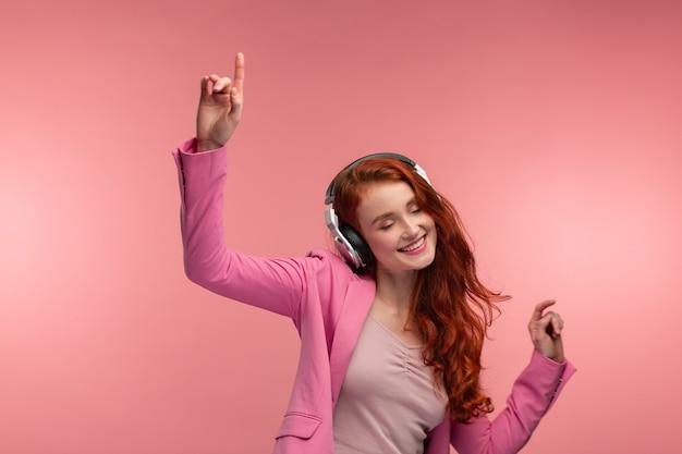 音楽をお楽しみください。音楽を聞いているヘッドフォンで美しい若い赤毛の女性
