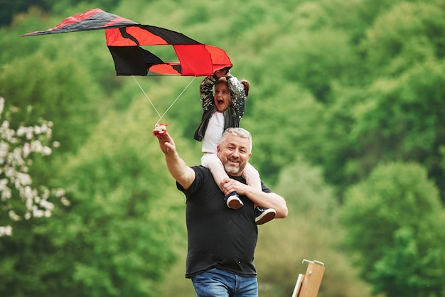 Enjoy the moment. running with red kite. child sitting on the man's shoulders. having fun