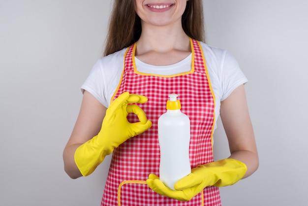 新製品フォームチェック会社コンセプトをお楽しみください。それを使用することをお勧めする手にディスペンサーとボトルを保持している美しい少女のトリミングされたクローズアップ写真