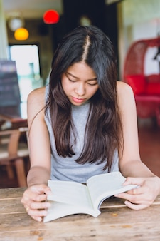 Enjoy relax times with reading book, asian women thai teen serious focus to read pocket book in coffee shop